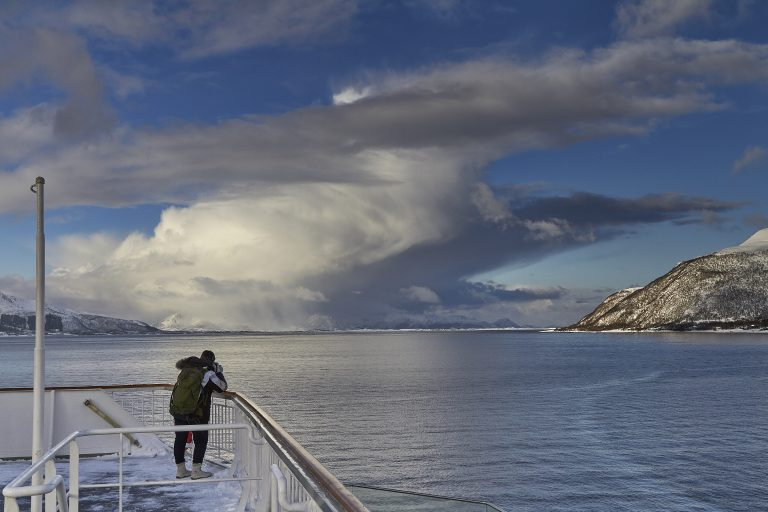 Eine Person fotografiert von einem Schiff aus die Natur aus. Man sieht das Meer, ein weißes Wolkengebilde und vereinzelt schneebedeckte Berge.