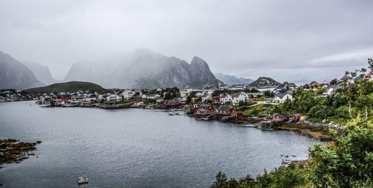 Der Blick in eine Bucht mit kleinem Fischerdorf. Es ist weiß bewölkt und im Hintergrund sind vernebelte Berge zu sehen.