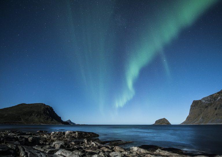 Ein Blick auf die grünen Nordlichter am blauen Sternenhimmel. Man sieht einen setinigen Boden der ins Meer führt und im Hintergrund sind einzele Berge zu sehen.